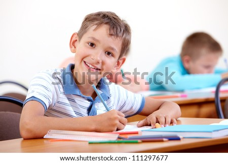 Portrait of smart lad looking at camera with classmates on background