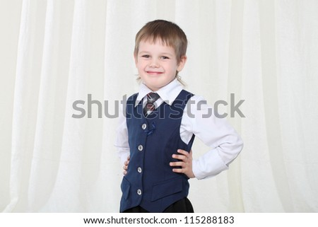 Portrait of smart little blond boy in suit at home