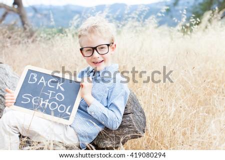 portrait of smart little boy in glasses holding blackboard ready for school enjoying autumn park, back to school concept - stock photo