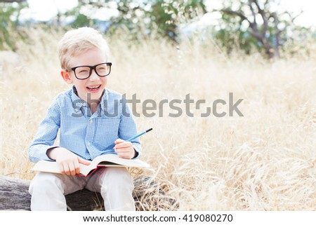 portrait of smart little boy in glasses holding book ready for school enjoying autumn park with copy space at his side - stock photo