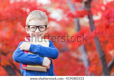 portrait of smart little boy in glasses holding book ready for school in beautiful autumn park