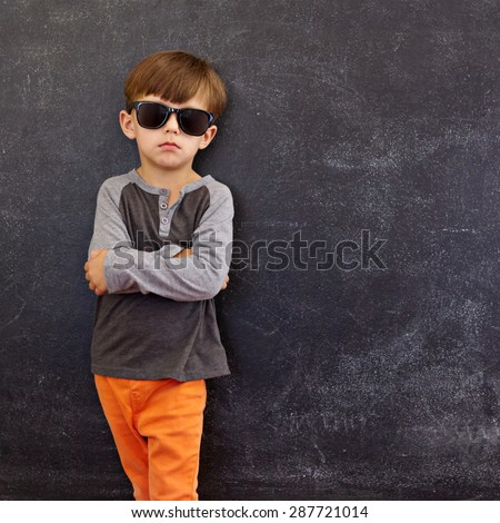 Portrait of smart little boy wearing sunglasses standing with his hands folded against blackboard with copyspace. - stock photo