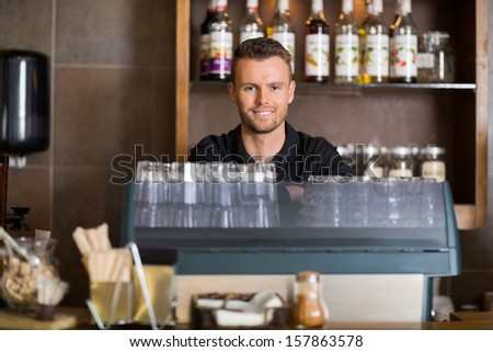 Portrait of smart male bartender at counter in cafe - stock photo