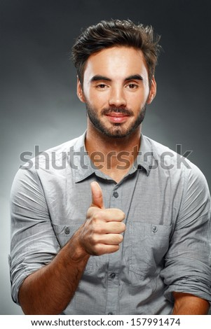 Portrait of smart man smiling and show giving you thumb up on dark studio background  - stock photo