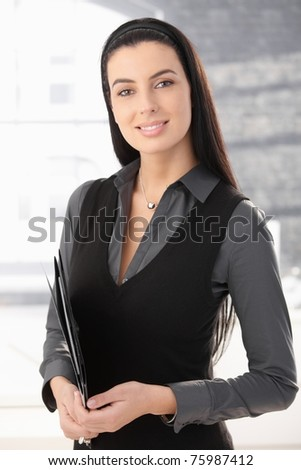 Portrait of smart office worker woman standing in office with document folder, smiling.? - stock photo