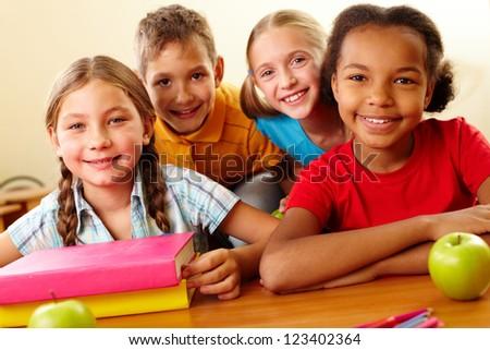 Portrait of smart schoolchildren looking at camera in classroom - stock photo