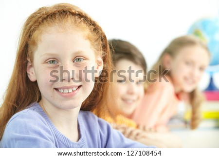 Portrait of smart schoolgirl looking at camera with classmates on background - stock photo
