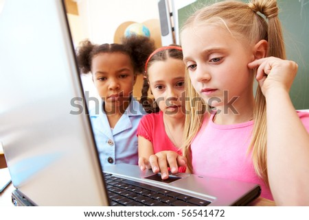 Portrait of smart schoolgirl looking at the laptop with her classmates on background - stock photo
