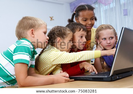 Portrait of smart schoolgirls and schoolboys looking at the laptop
