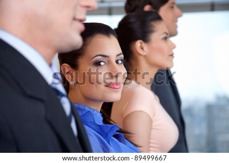 Portrait of smart smiling businesswoman with colleagues standing in a row - stock photo