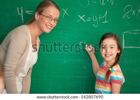 Portrait of smart teacher and schoolgirl standing by blackboard and looking at camera - stock photo