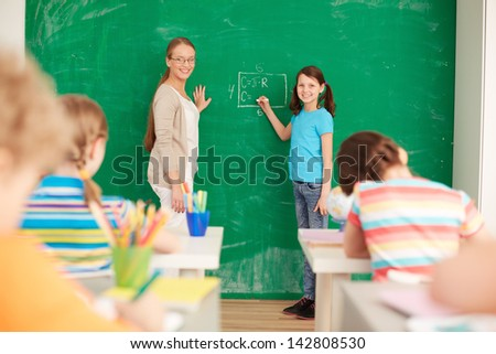 Portrait of smart teacher and schoolgirl standing by blackboard and looking at schoolkids in classroom - stock photo