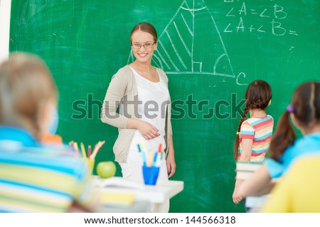 Portrait of smart teacher standing by blackboard and looking at schoolkids while one of pupils standing near by - stock photo