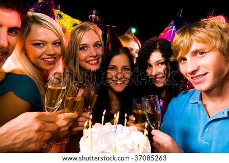 Portrait of smart teens with birthday cake and champagne flutes looking at camera