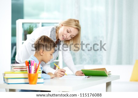 Portrait of smart tutor with pencil correcting mistakes in pupil�¢??s notebook - stock photo