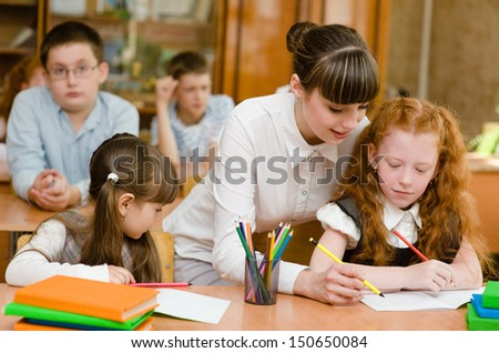 Portrait of smart tutor with pencil correcting mistakes in pupils notebook