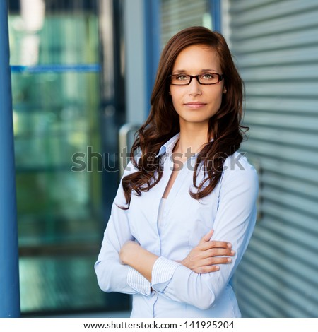 Portrait of smart woman posing with arms crossed outdoors - stock photo