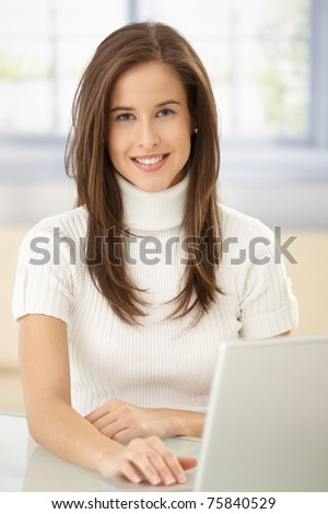 Portrait of smart woman with laptop computer, smiling at camera.?