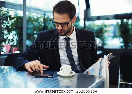Portrait of smart young businessman in glasses touching screen of digital tablet while drink coffee at his breakfast, business and technology concept - stock photo