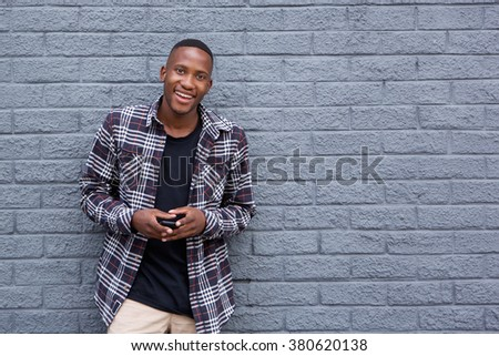 Portrait of smart young man standing against a gray wall holding a mobile phone and smiling - stock photo