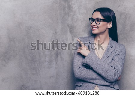 Portrait of smart young successful businesswoman in glasses and suit pointing to the side while standing near gray wall.