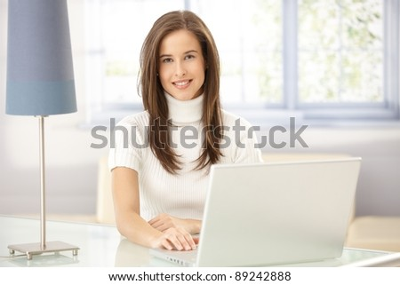 Portrait of smart young woman sitting at table in study, using laptop computer, looking at camera.? - stock photo