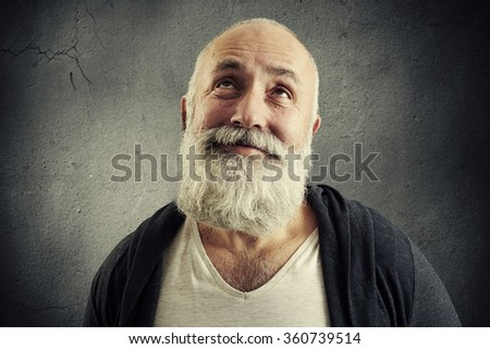 portrait of smiley bearded man looking up over dark background