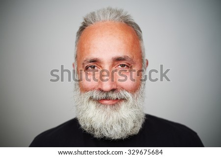portrait of smiley bearded man over grey background