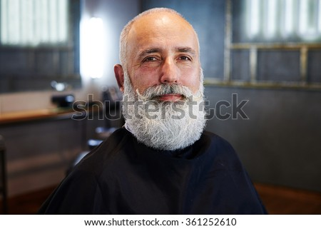 portrait of smiley bearded senior man in barber shop