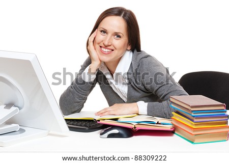 portrait of smiley student with books sitting on workplace