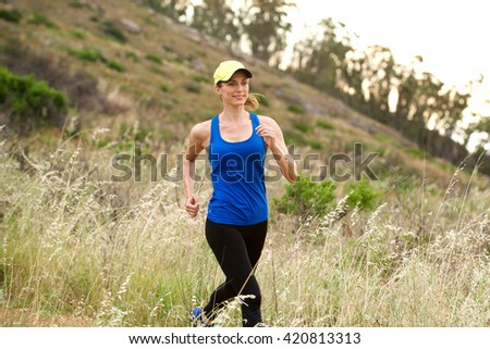 Portrait of smiling active woman running on trail training outside