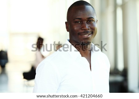 Portrait of smiling African American business man with executives working in background  - stock photo