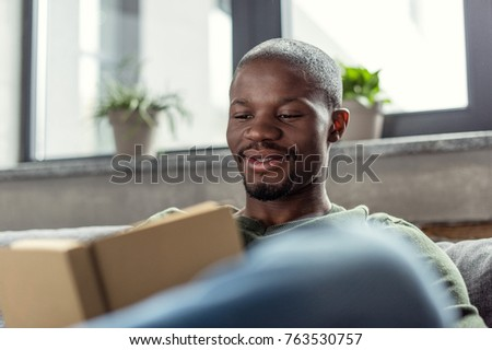portrait of smiling african american man reading book at home