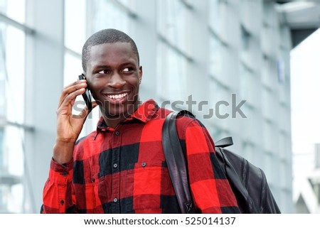 Portrait of smiling african student with bag talking on phone