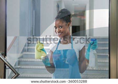 Portrait Of Smiling African Woman Cleaning Glass With Rag - stock photo