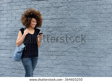 Portrait of smiling african woman walking with cell phone - stock photo