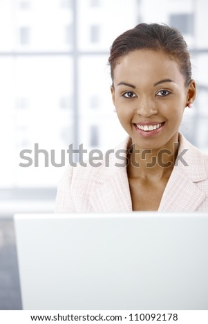 Portrait of smiling afro businesswoman using laptop computer in office, looking at camera. - stock photo