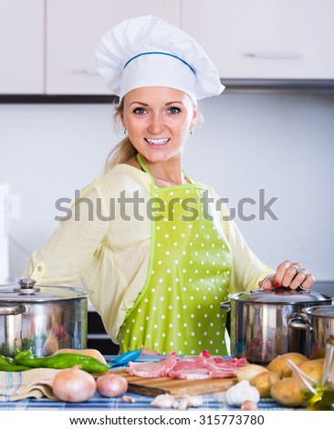 Portrait of smiling american blonde girl preparing meat indoors