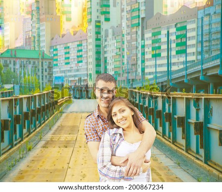 Portrait of Smiling and embracing young adult couple standing on old rusty metal bridge in front of town houses background Copy space for inscription - stock photo