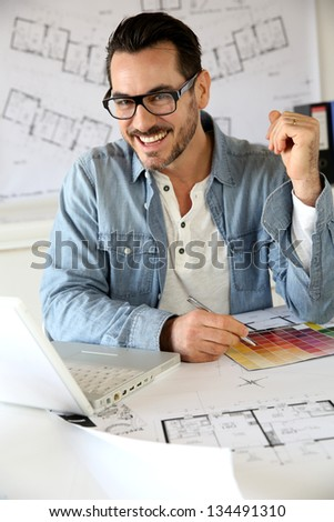 Portrait of smiling architect working in office - stock photo