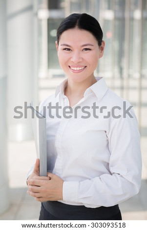 Portrait of smiling asian businesswoman. Pretty lady in white shirt with grey folder isolated on the territory of modern building.