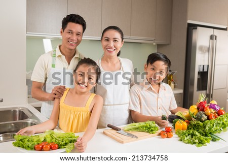 Portrait of smiling Asian family standing in the kitchen with vegetables on the table - stock photo