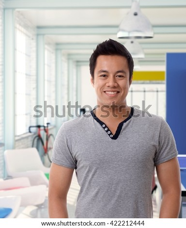 Portrait of smiling asian man in casual tshirt at modern office.
