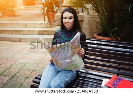 Portrait of smiling asian woman sitting on the bench with open city map and look to the camera, brunette hair tourist girl enjoying her vacation travel in Barcelona, flare sunset light, cross process - stock photo