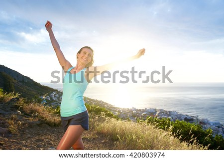 Portrait of smiling athletic woman with arms outstretched  - stock photo