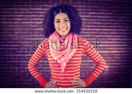 Portrait of smiling attractive woman with hands on hips against red brick background - stock photo