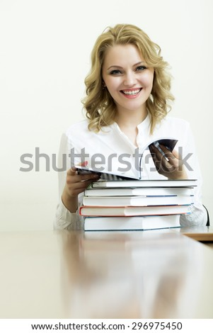 Portrait of smiling attractive young student girl with blonde curly hair in blouse sitting at table with heap of books holding and reading on white wall background copyspace, horizontal picture - stock photo