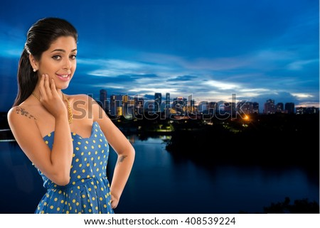 Portrait of smiling attractive young woman against night city - stock photo