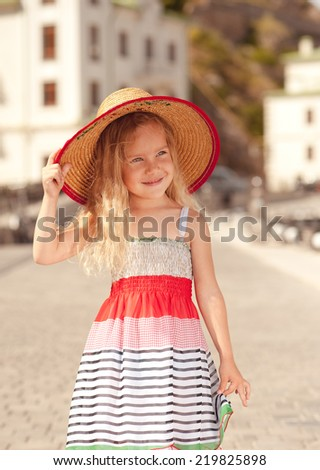 Portrait of smiling baby girl walking in city outdoors - stock photo