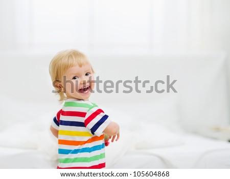 Portrait of smiling baby in bedroom - stock photo